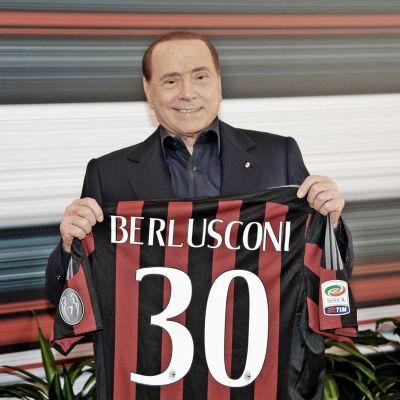 Silvio Berlusconi håller upp en Milantröja med nummer 30 på.