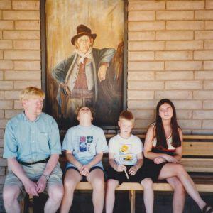Penkillä seinän vieressä istuvat isä ja hänen kolme lastaan: tytär, poika ja tytär.