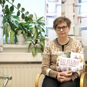 Kajaanin perheasiain neuvontakeskuksen johtaja Aune Hiltunen pitää Halataan-kampanjan julistetta.