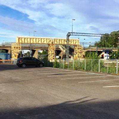 I förgrunden en tom asfalterad parkering. Längre borta syns en bro över en bangård samt en tillfälllig träbro. Karis järnvägsstations, en gul stockbyggnad, syns till höger.