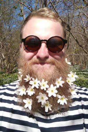 Jonas Forsbacka med blommor i skägget.