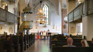 Längst fram syns altaret i Borgå domkyrka och fyra sjungande kvinnor. I bänkraderna sitter en hel del människor, främst unga par.