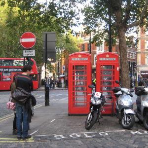 Moottoripyöriä parkissa punaisten puhelinkioskien edessä Lontoossa.