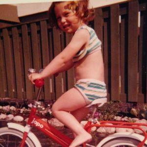 Noin kuusi vuotias tyttö punaisen Jopo-polkupyöränsä selässä äitinsä tekemissä bikineissään.