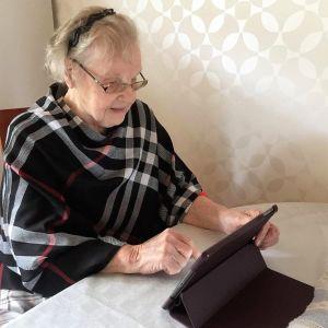 Äldre kvinna ser på en surfplatta