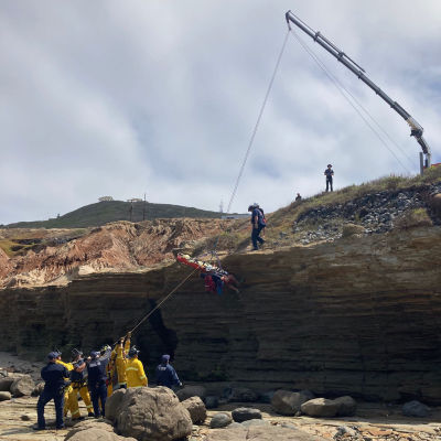 Räddningsarbetare hissar upp en skadad person längs en klippvägg i San Diego.