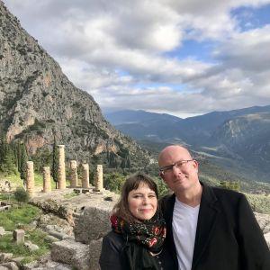 Pariskunta poseeraaa temppelin raunioiden edessä. Takana näkyy vuoria.