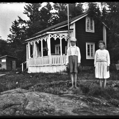 Svart-vit bild av två barn framför ett sommarhus.