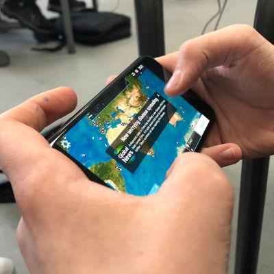 Nuori pelaa mobiilipeli Plague Inc:iä kännykällä.