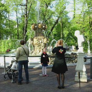Tyttö poseeraa äidille suihkulähteen edessä Pietarin Kesäpuistossa