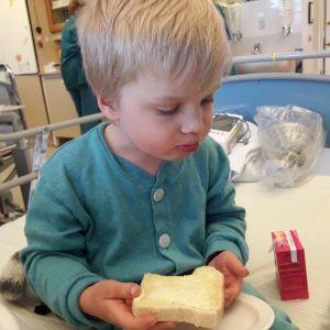 Lapsi sairaalan vuoteen reunalla. Syö leipää
