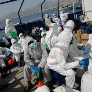 De migranter som räddats av det spanska räddningsfartyget Aita Mari, fick klä på sig skyddsdräkter och fördes vidare till den italienska passagerarfärjan på söndagen.