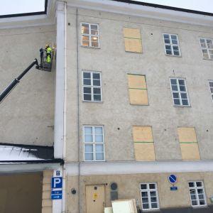 Rapattu vanha koulurakennus, jonka ikkunoita korjataan.