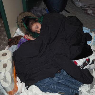 Irakiskt barn sover på wc-papper i cykelförvaret på nattåget från Kemi söderut.