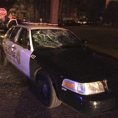 En polisbil har blivit sönderslagen av demonstranter.