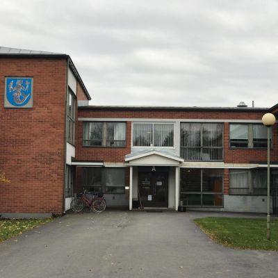 Vörå kommungård fotad från utsidan rakt mot ingången. Byggnaden är i tegel.