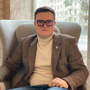 En ung man i brun kostym och glasögon sitter i en fotölj. Han ser allvarligt in i kameran.