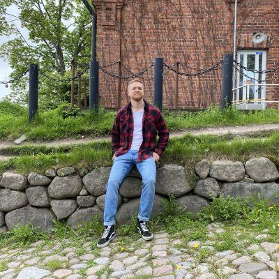 Tuomo Vento istuu Lappeerannan linnoituksen kivimuurilla