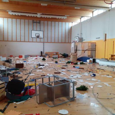 En gymnastiksal som blivit utsatt för skadegörelse. På golvet ligger en massa bråte.