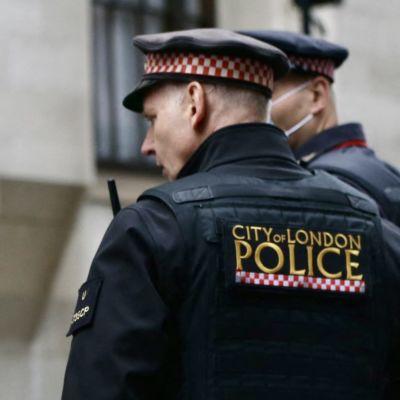"""Poliser i London står med ryggen mot kameran. På deras rygg står """"City of London police"""". De är klädda i uniform."""