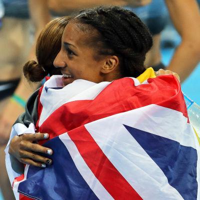 Sjukampare kramar om varandra omsvepta av en brittisk flagga.