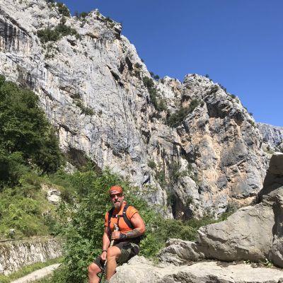 Björn Roos sitter på en sten i ettt bergit landskap.
