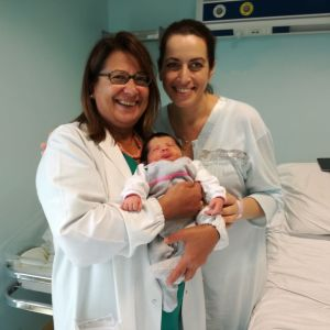 Läkaren Anna tillsammans med en nyförlöst mamma och hennes bebis