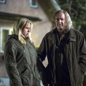 Karaktärerna Vera och Torsten står på en mörk gårdsplan.