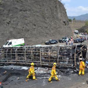 En buss ligger på sidan efter att ha krockat och börjat brinna i Mexiko.