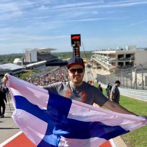 En glad man med solglasögon och keps och finländsk flagga dtår på en sportplan.