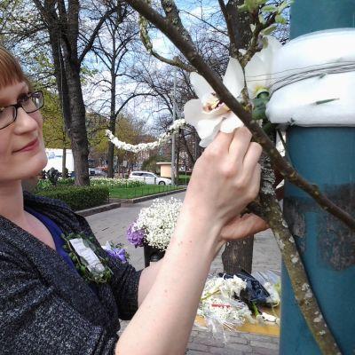 Floristi Tiina Pulkkinen asettelee orkideoita pylvääseen.
