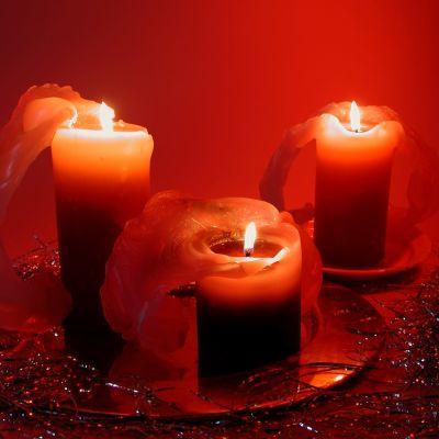 Tre stycken röda, brinnande ljus mot en röd bakgrund.