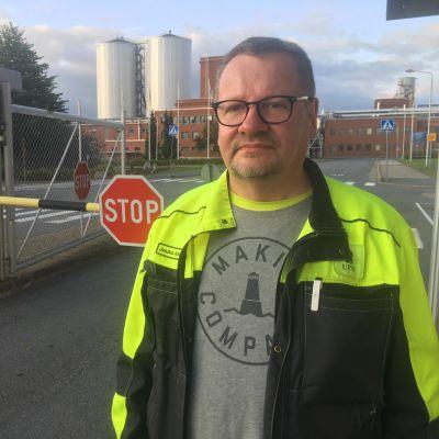 Mies seisoo tehtaan pääportin edustalla.