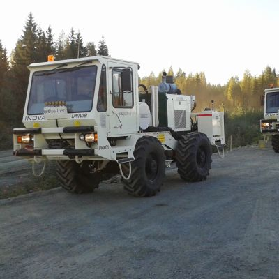 Kaksi maaperää tutkivaa autoa metsätiellä.