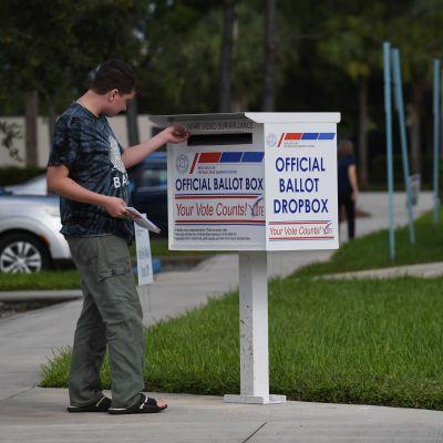 Mies laittaa kirjekuorta äänestyspostille tarkoitettuun laatikkoon.