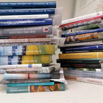 Pöydällä on kahdessa pinossa Vuoden kotiseututeos -kilpailuun osallistuvia kirjoja.