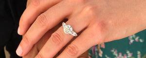 En kvinnohand vars ringfinger pryds av en silvrig förlovningsring med en stor gnistrande diamant