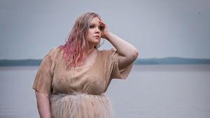 Kvinna i beige klänning och blont och rosa hår. Hon står på klippor framför havet och tittar ut till höger och håller handen mot pannan och sidan av huvudet.