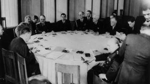 Män i kostymer sitter runt ett bord.