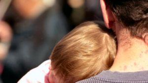 Isä pitää lasta sylissä