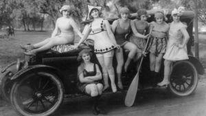 En grupp kvinnor poserar vid en bil. Svartvit bild.