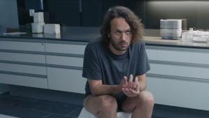 Huvudpersonen sitter och svalkar rumpan i en skål med is.
