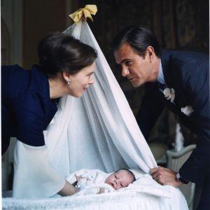 Man och kvinna lutar sig över baby som ligger i vagga
