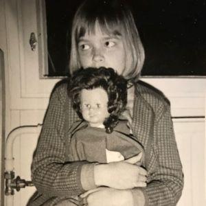 Kirjailija Kati Tervo 8-vuotiaana totisena nukke sylissään, osin kasvojen edessä.