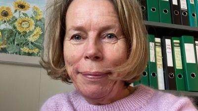 En leende kvinna som sitter i ett arbetsrum.