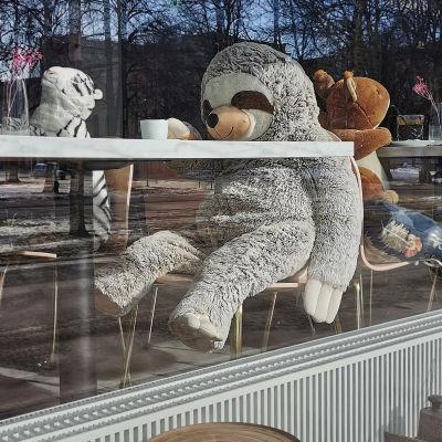 Ett cafés sittplatser intill fönstret mot gatan har fyllts av mjukisdjur under stängningen under coronapandemin.