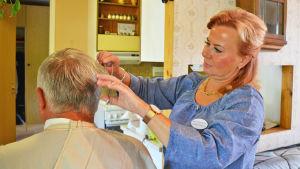 En kvinna i blå skjorta klipper håret på en äldre man.