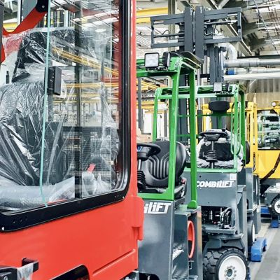Gaffeltruckar står på rad i färggranna färger på företaget Combilifts fabrik i Monaghan på Irland.