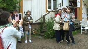 Japans turistgrupp fotograferar utanför butik.