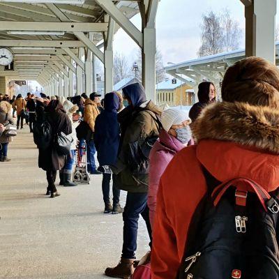 Mänskor väntar på ett försenat tåg på en full perrong på tågstation i Tartu, Estland.